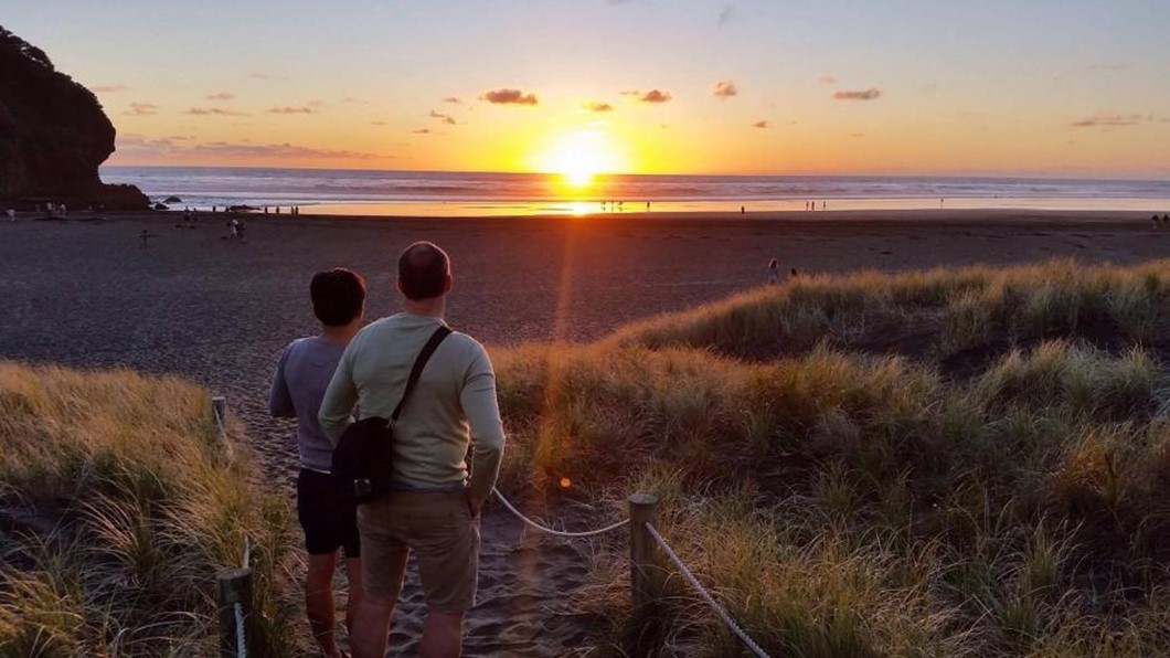 Couple viewing the beautiful sunset on New Zealand beach.